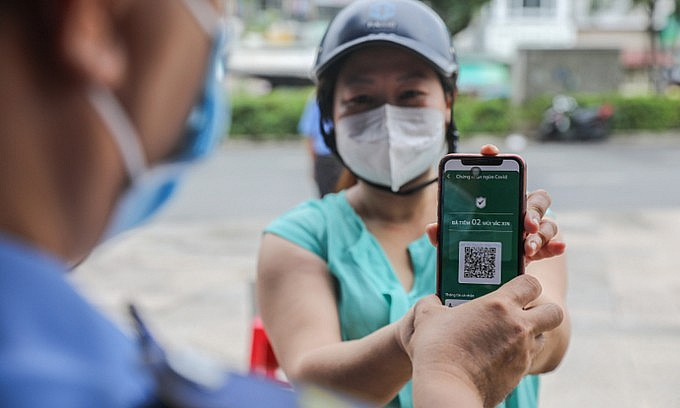 A woman shows her vaccine status to a security guard at a supermarket in Ho Chi Minh City on October 6, 2021. Photo: VnExpress