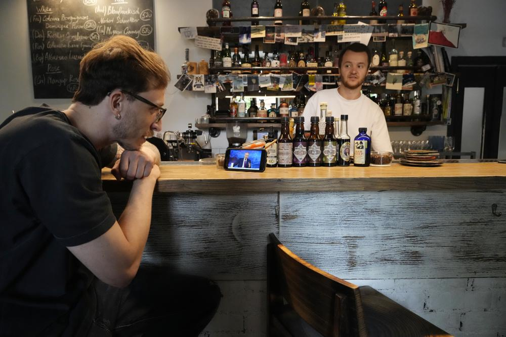 A bartender watches his smartphone showing a live stream of Russian President Vladimir Putin's annual televised call-in show, in a bar in Moscow, Russia, Wednesday, June 30, 2021.  Photo: AP