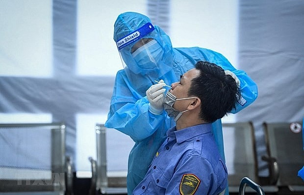 A medical worker takes sample for Covid-19 testing. Photo: VNA